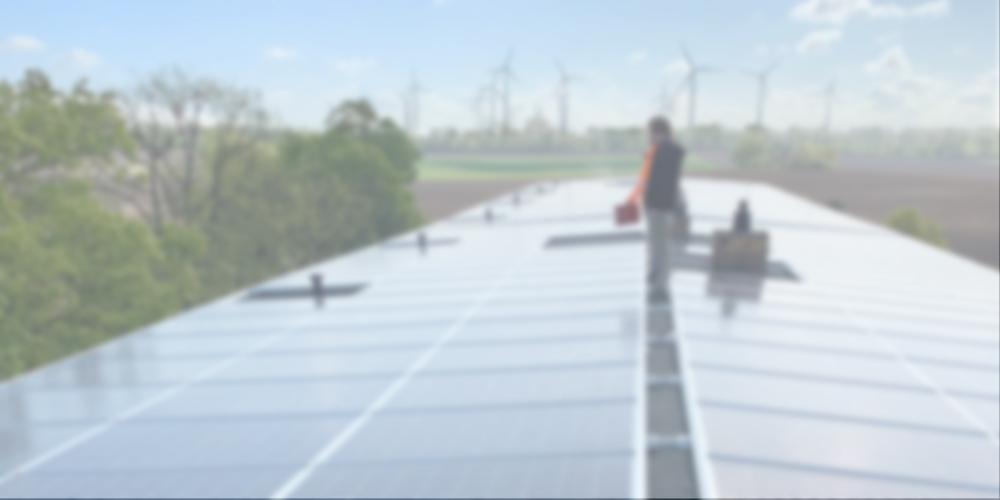Personen auf einem Dach bei der Installation einer PV-Anlage, Windräder im Hintergrund